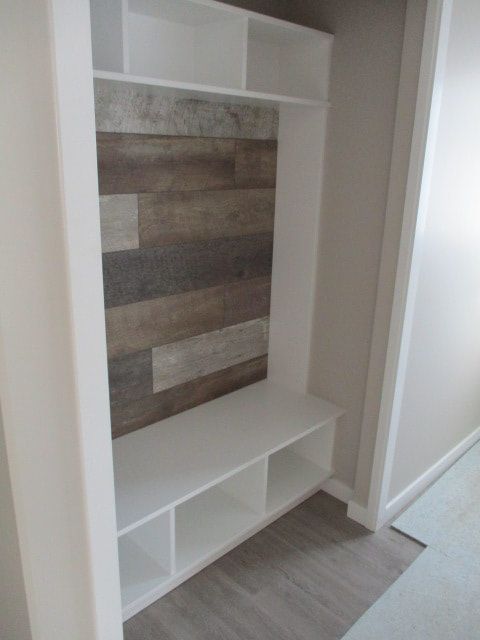 White shelving and wood wall feature inside RTM