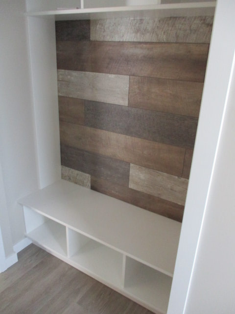 Cubicle shelves inside RTM home with wooden wall feature
