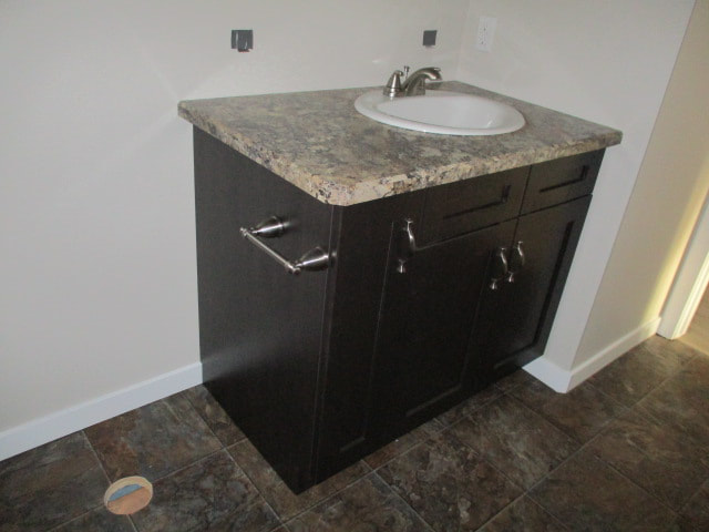 Bathroom vanity with brown marble counter and brown cabinets