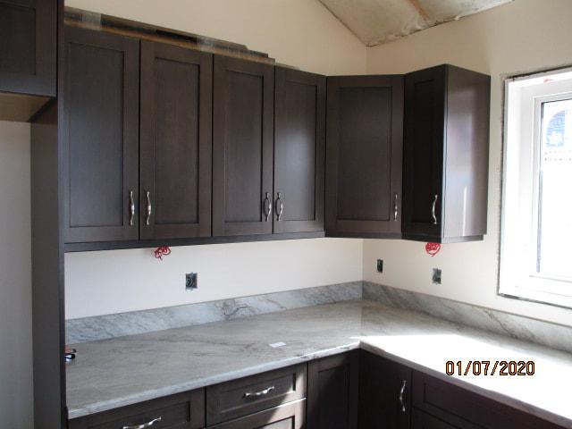 Dark wood cupboard kitchen with marble countertop
