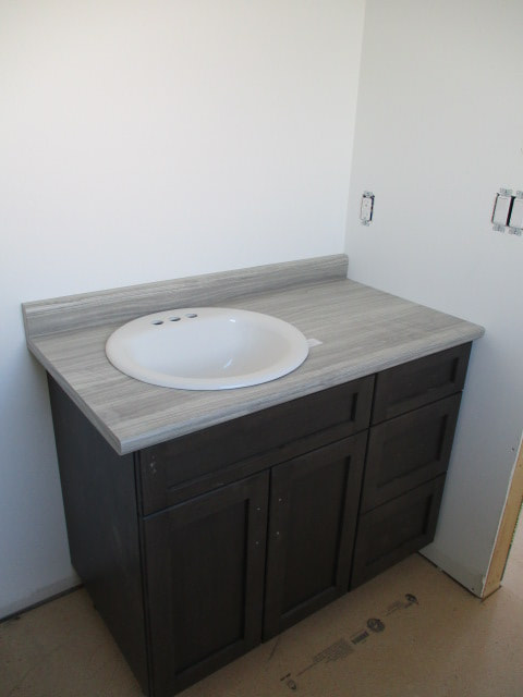 Grey bathroom countertop with white sink and brown cabinet RTM