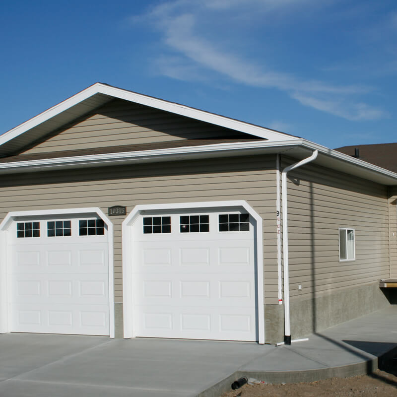 Two car garage with white doors and brown house